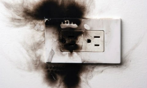 electrical outlet charred and showing dark burn marks on a white wall