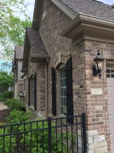 A home in Aurora that has electrical lighting installed on the brick exterior.